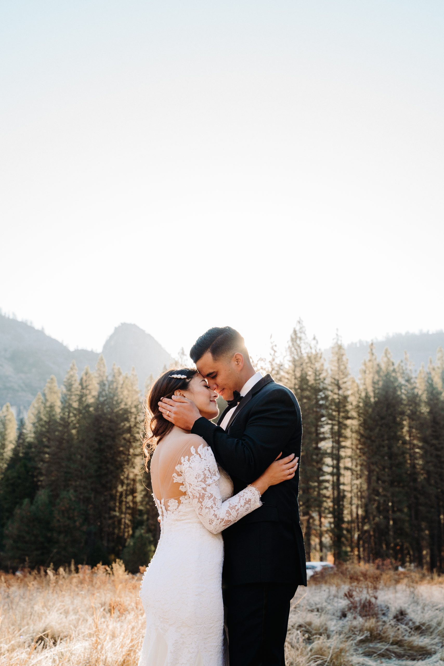 A husband embracing his wife at Yosemite California during their adventurous day-after elopement photo session in their wedding attire.