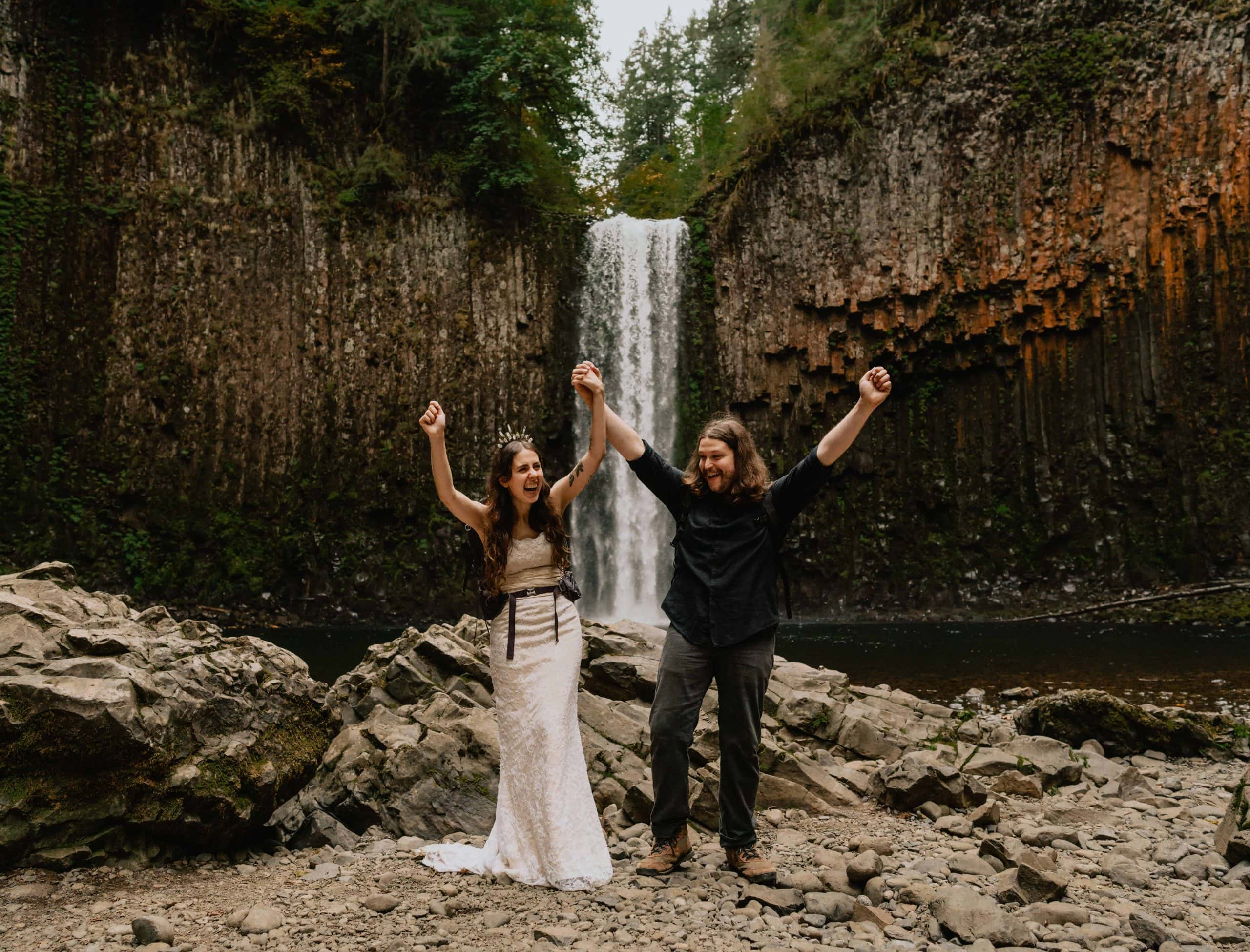 A couple cheering while wearing their backpacks during their adventurous waterfall elopement in Portland Oregon.