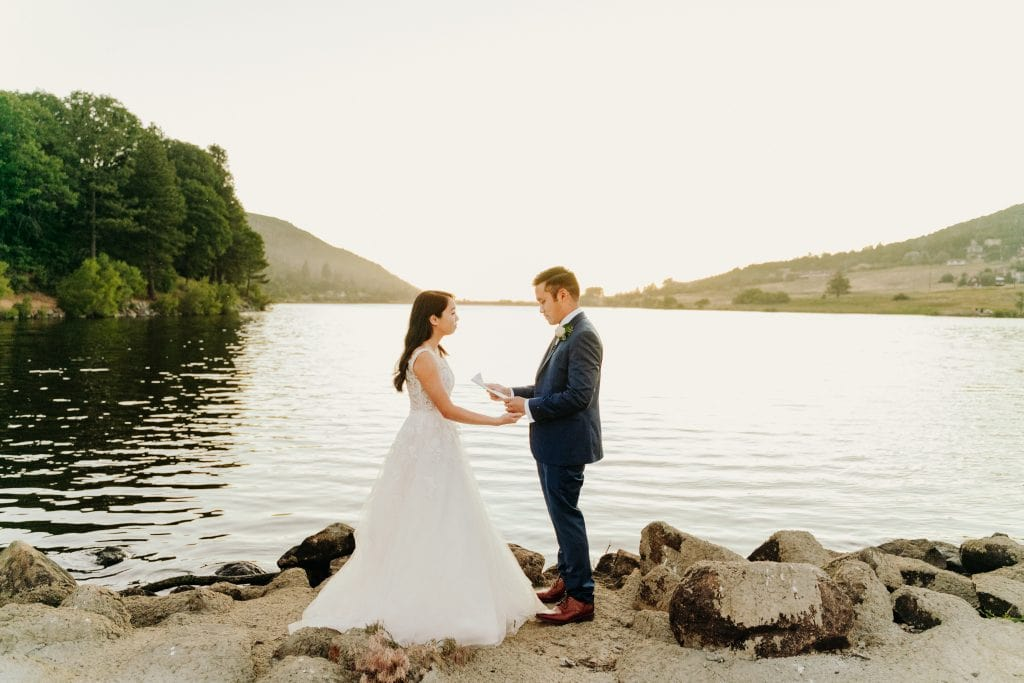 A couple reading their vows during their lakeside San Diego elopement.