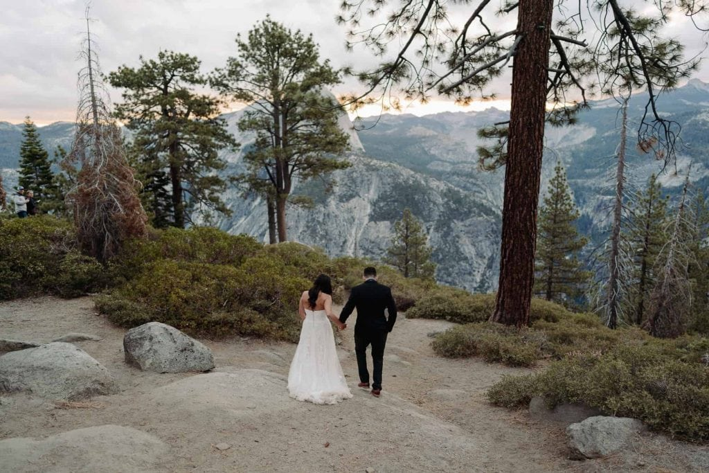 A couple holding hands as they walk down towards Glacier Point at Yosemite, California.