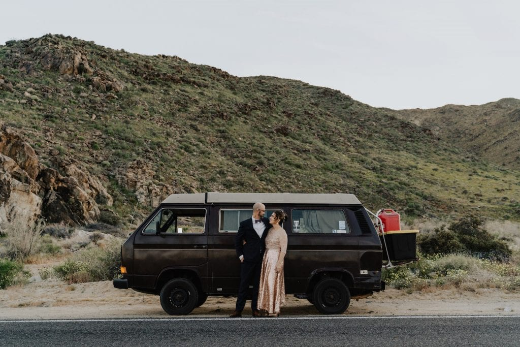 A couple embracing and staring into each others eyes as they prepare to get into their Volkswagen Beetle during their adventurous desert elopement in Joshua Tree California.