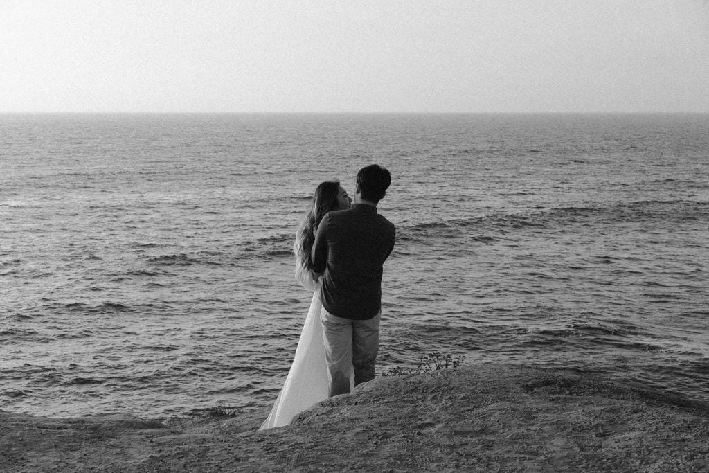An eloping couple embracing while staring into the ocean during their beach elopement in San Diego, California.