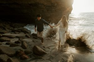 A couple holding hands and running through the ocean water with a wave crashing behind them during their Sunset Cliffs engagement session in San Diego, California.