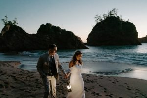 Couple holding lanterns along the coast during their Oregon Elopement